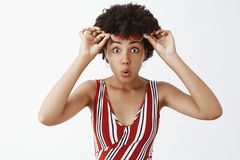 You gotta be kidding, amazing sale. Impressed attractive African American girl with curly hairstyle, taking off. Sunglasses and staring curious and amazed at stock images