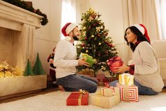 Happy couple exchanging Christmas presents. Only for you. Happy international couple in Santa hats sitting on the floor near a Christmas tree and exchanging Royalty Free Stock Photography