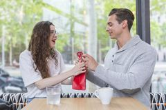 Happy young couple sitting at the cafe table with a present royalty free stock images