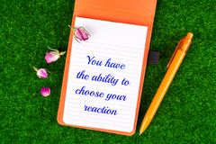 You have the ability to choose your reaction. In notebook with dried rose bud and pen on grass background Stock Photos