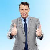 You have done a great job, keep up!. Successful entrepreneur showing double thumbs up Stock Photo