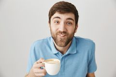 You have something on your moustache. Portrait of funny playful bearded guy drinking cup of cappuccino and having milk. On face, smiling and being carefree Royalty Free Stock Images