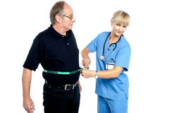 You have surely lost some weight. Pretty female doctor measuring waist of senior surprised man royalty free stock photos