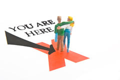 You Are Here. Miniature couple on X with you are here text Royalty Free Stock Images