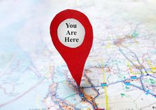 You Are Here locator. Red locator symbol on a map with You Are Here text royalty free stock photography