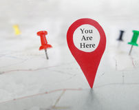 You Are Here locator symbol. On a map with tacks royalty free stock photography