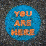 You Are Here, Sign Painted on Pavement. You Are Here. Funny Obvious Circular Public Park Sign Painted on Pavement. Colorful Blue Orange Close-up Texture Abstract Stock Images