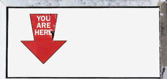 You Are Here Sign. Somewhat ragged red arrow on YOU ARE HERE sign attached to wall. Lots of copy space stock images