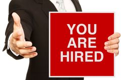 You Are Hired. A businessman offering a handshake and holding a recruitment signboard Royalty Free Stock Images