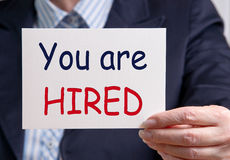 You are hired. Businesswoman, in suit, shirt and tie,  holding white sign with text 'you are hired' where the word hired is in uppercase red letters Royalty Free Stock Photo