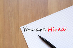 You are hired concept. White blank notepad on office wooden table You are hired concept Royalty Free Stock Images