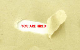 YOU ARE HIRED. Text YOU ARE HIRED appearing behind torn light brown envelope Royalty Free Stock Photography