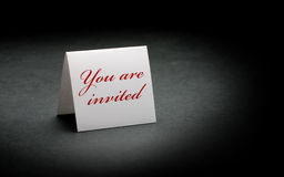 You are invited. Written in red on a white sign. image is over a black paper background Stock Image