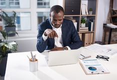 Qualified manager is feeling annoyance while having online communication. You. irritated young african businessman sitting at table in office and having video Royalty Free Stock Photo