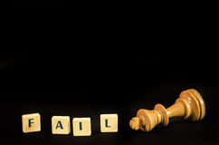You just failed. Fail word tiles with knocked over white king isolated on black Royalty Free Stock Photo