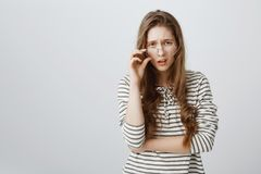 Are you kidding me. Studio shot of good-looking puzzled girl with fair hair, frowning, looking from under forehead. Taking off glasses and looking with Royalty Free Stock Photos