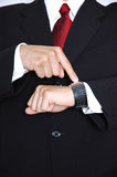 You are late. Business man in black suit wearing red power tie pointing to his watch royalty free stock photo