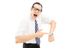 You are late. Angry man shouting and pointing on a wrist watch isolated against white background Royalty Free Stock Photos