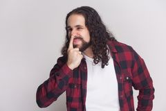 You are liar. angry man with beard and black long curly hair in. Casual style, checkered red shirt standing, looking away and showing lie gesture. indoor studio royalty free stock image