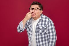 You are liar. Portrait of middle aged business man in casual checkered shirt and eyeglasses standing and showing lie gesture. Touching his mose. indoor studio royalty free stock image