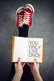 You Only Live Once Concept. You Only Live Once or YOLO Concept with Young Woman Reading Book with Her Feet Raised in The Air Stock Photo