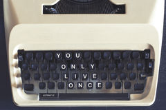 You Only Live Once motivational message. You Only Live Once (YOLO)  motivational message written on vintage typewriter keys Stock Image