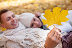You are love of all my life. Attractive young loving couple is lying on the blanket in the autumn park. They are embracing and smiling. The men is holding a Royalty Free Stock Images