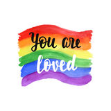 You are loved badge. Inspirational Gay Pride poster with watercolor rainbow spectrum flag, brush lettering. Homosexuality emblem. LGBT rights concept Royalty Free Stock Image