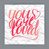 You are loved. Hand-drawn quote on crumpled paper background Royalty Free Stock Photos