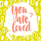 You are loved lettering. You are loved. Vector motivation and inspirational quote on a bright abstract yellow background.. Hand lettering. Typographical element Stock Photos
