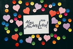You are loved - text on black background with hearts decorations. Religion and feelings concept royalty free stock images