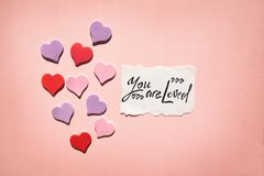 You are loved - text on pink background with hearts, religion and feelings concept. You are loved - black text on pink background with hearts, religion and royalty free stock images
