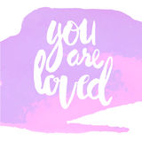 You are loved. Violet lettering You are loved  hand brush Stock Photo