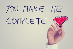 You Make Me Complete. Man writing an inspirational message of love on a virtual interface with the words - You Make Me Complete - with a red heart and copyspace royalty free stock photos