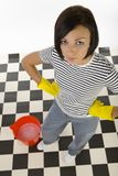 You make a mess and I must clean it. Young woman in yellow rubber gloves standing with hands on hips beside red bucket. Looking at camera, high angle view. Whole stock photo