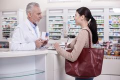 Happy male pharmacist helping client Royalty Free Stock Images