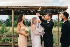 You may kiss the bride. Handsome groom lifting up bridal veil to kiss beautiful bride. Couple having an outdoor wedding ceremony. Bride and groom about to kiss Stock Photography