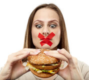 You may not eat junk food!. Young woman with duct tape over her mouth, preventing her to eat junk food. Healthy eating concept stock photos