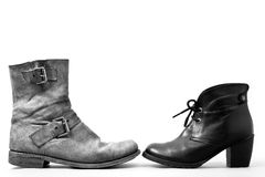 You and me. View of a pair of isolated different boots (for men and women). Concept of couple Royalty Free Stock Photography