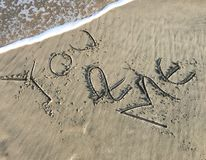 You and Me letter drawn on beach sand with sea waves stock image