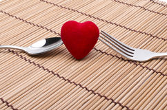 You and me and love. Red heart between silver fork and spoon on a bamboo background stock image