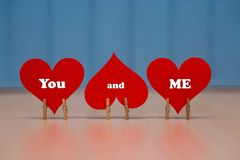 `You and me` text on red paper heart on table. With blue wooden background Stock Image