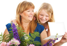 For You Mom. Mother with flowers and a card from her daughter.  Birthday or Mother's Day concept Stock Image