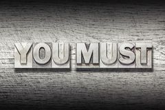 You must met. You must phrase made from metallic letterpress on rough wooden texture Stock Photography