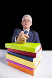 You must read books. Senior teacher portrait behind some books pointing to you (isolated on black stock photography