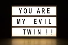 You are my evil twin light box sign board. On wooden table stock photo