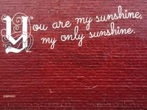 You are my only sunshine brick wall. Red brick wall with beautiful graffiti art that says you are my only sunshine Stock Image