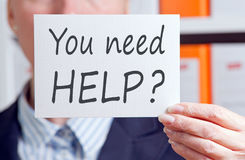 You need help - Businesswoman holding card with text. You need help - Businesswoman holding white card with text in the office stock images