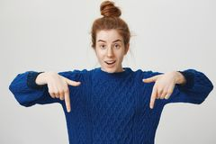 You never believe what I saw downstairs. Portrait of emotive excited good-looking girl with ginger hair pointing down. And glancing at camera, expressing Royalty Free Stock Photo