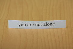 You are not alone. The phrase you are not alone typed on a strip of paper left standing on a wooden desktop background Royalty Free Stock Images